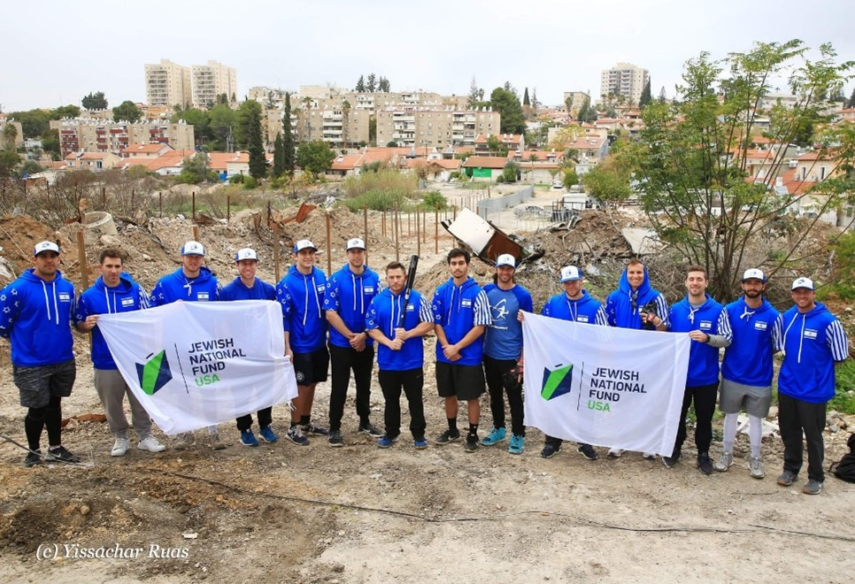 Team Israel players hold Jewish National Fund-USA banners at the Project Baseball field in Beit Shemesh (photo courtesy Israel Baseball)
